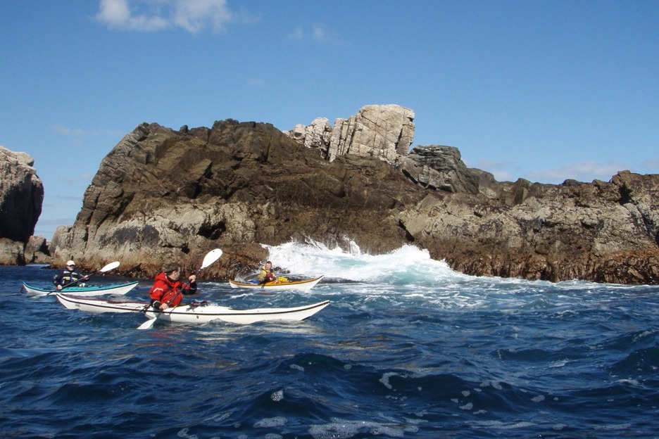 Three sea kayakers in Scotland